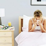 Young Woman Blowing Her Nose in Bed --- Image by � Royalty-Free/Corbis